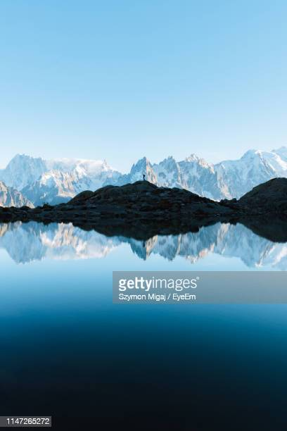 scenic view of lake and snowcapped mountains against clear blue sky - schöne natur stock-fotos und bilder