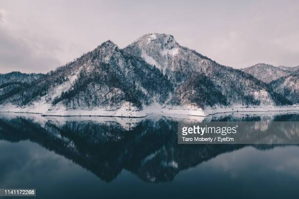 scenic view of lake and snowcapped mountains against sky - sapporo stock pictures, royalty-free photos & images