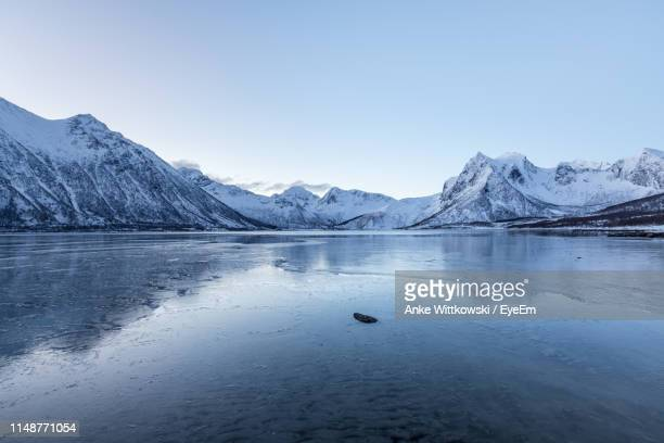 scenic view of lake and snowcapped mountains against sky - snowcapped mountain stock pictures, royalty-free photos & images