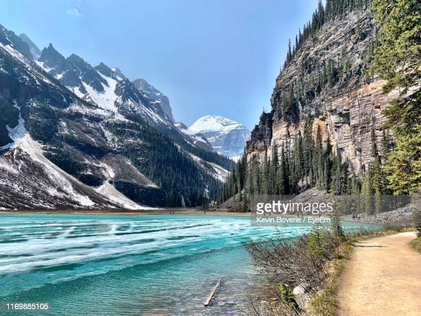 scenic view of lake and snowcapped mountains against sky - lake louise stock pictures, royalty-free photos & images
