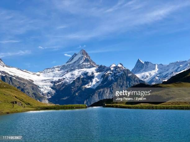 "scenic view of lake and snowcapped mountains against sky - ""jörg peters"" stock-fotos und bilder"