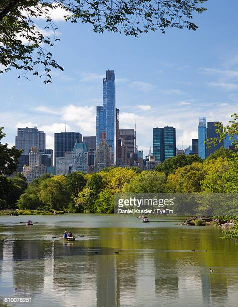 scenic view of lake and trees against sky in city on sunny day at central park - waterkant stockfoto's en -beelden