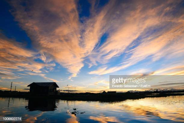 scenic view of lake by building against sky during sunset - central kalimantan stock pictures, royalty-free photos & images