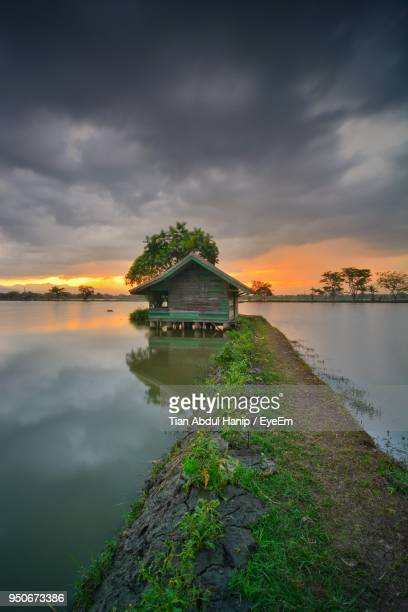 scenic view of lake by building against sky during sunset - tian abdul hanip stock photos and pictures