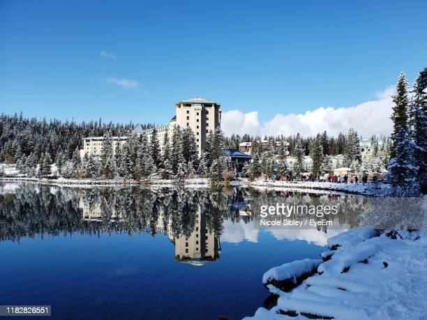 scenic view of lake by building against sky during winter - sibley stock photos and pictures