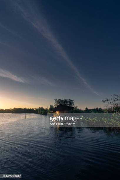scenic view of lake by building against sky - ade rizal stock photos and pictures
