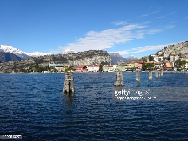 scenic view of lake by buildings against blue sky - kanjana kongthong foto e immagini stock