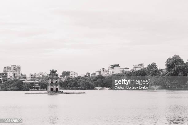 scenic view of lake by buildings against sky - bortes ストックフォトと画像