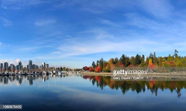 scenic view of lake by buildings against sky - vancouver stock pictures, royalty-free photos & images