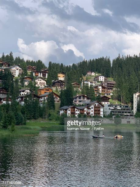 scenic view of lake by buildings against sky - アロサ ストックフォトと画像