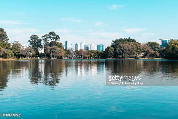 scenic view of lake by buildings against sky - ibirapuera park stock pictures, royalty-free photos & images