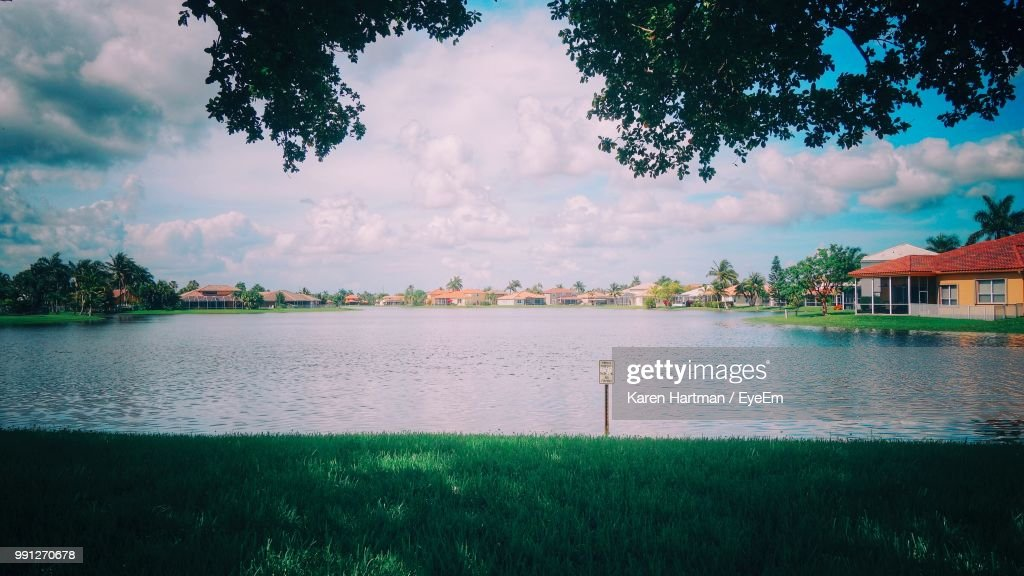 Scenic View Of Lake By Buildings Against Sky : Stock Photo