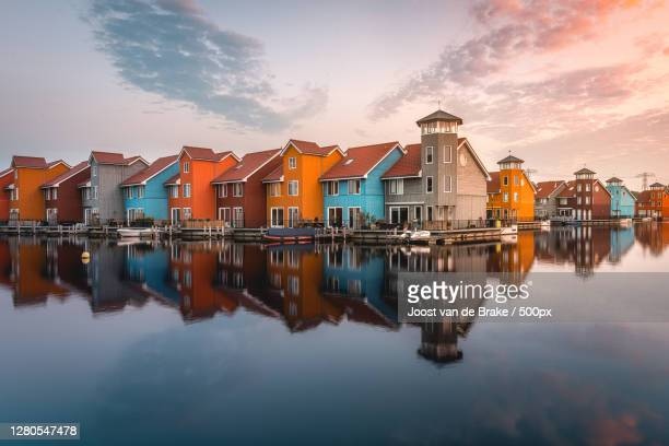 scenic view of lake by buildings against sky,groningen,netherlands - netherlands stock pictures, royalty-free photos & images