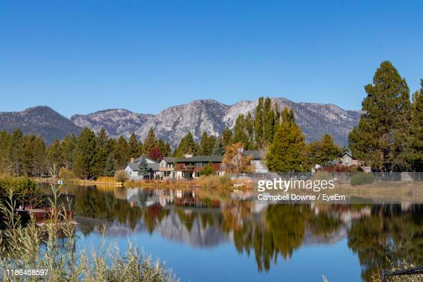 scenic view of lake by buildings and mountains against clear sky - campbell downie stock pictures, royalty-free photos & images