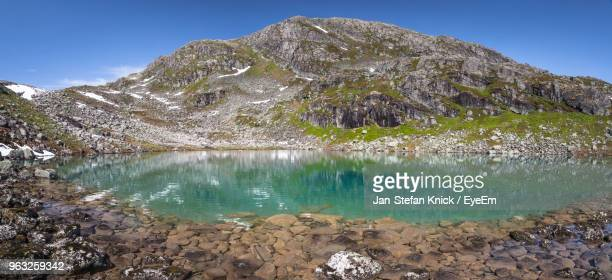 Scenic View Of Lake By Mountain Against Blue Sky