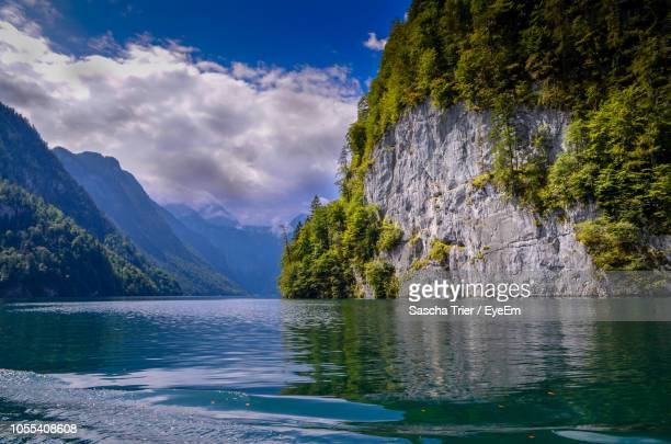scenic view of lake by mountain against sky - pinaceae stock pictures, royalty-free photos & images
