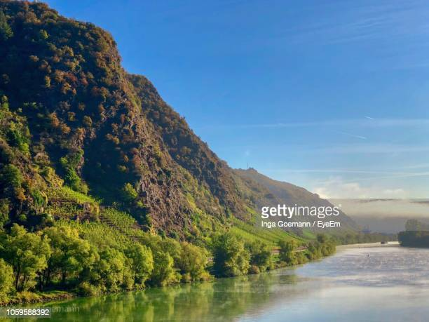 scenic view of lake by mountain against sky - moseltal stock-fotos und bilder