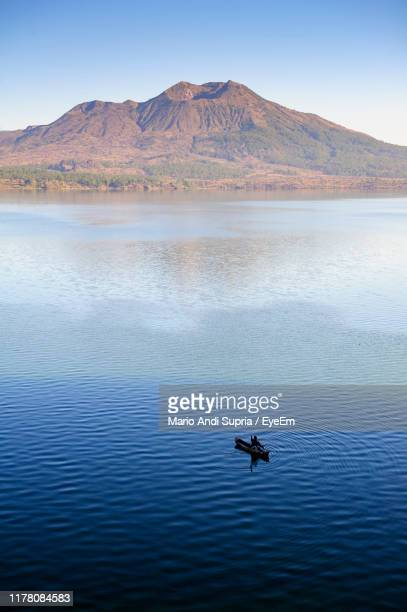 scenic view of lake by mountain against sky - kintamani district stock pictures, royalty-free photos & images