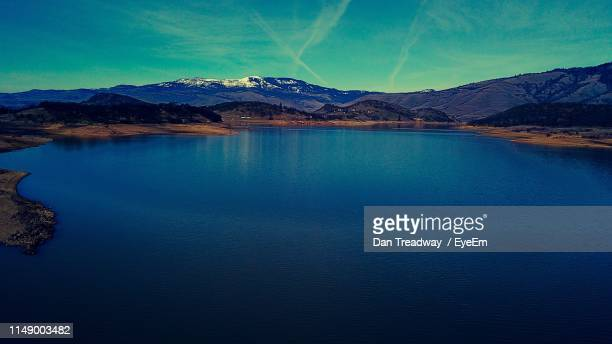 scenic view of lake by mountains against blue sky - dan peak stock photos and pictures