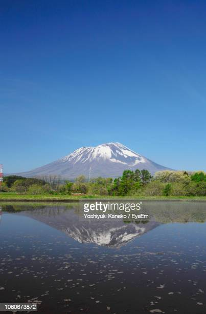 scenic view of lake by mountains against clear blue sky - 盛岡市 ストックフォトと画像