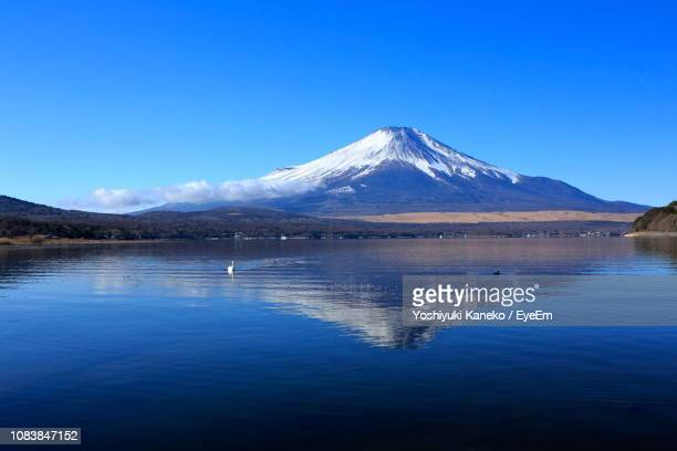 scenic view of lake by mountains against clear blue sky - yamanashi prefecture stock pictures, royalty-free photos & images