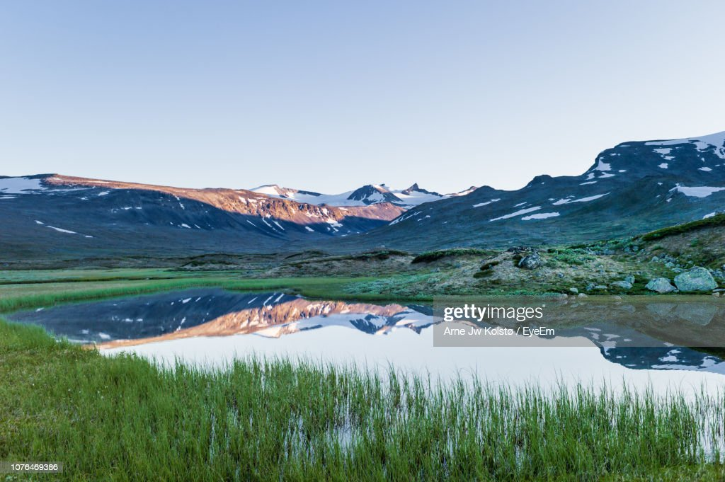 Scenic View Of Lake By Mountains Against Clear Sky : Stock Photo