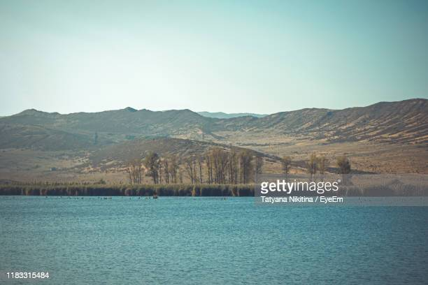 scenic view of lake by mountains against clear sky - nikitina stock pictures, royalty-free photos & images