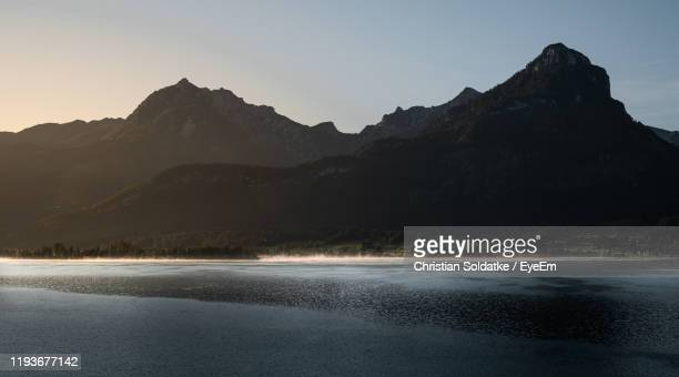 scenic view of lake by mountains against clear sky - christian soldatke stock pictures, royalty-free photos & images