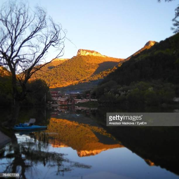 scenic view of lake by mountains against clear sky - anastasi foto e immagini stock