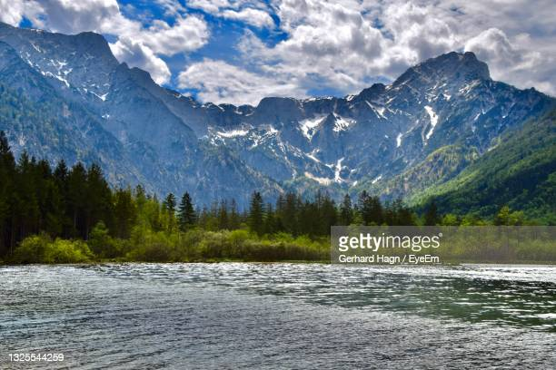scenic view of lake by mountains against cloudy sky - gerhard hagn stock-fotos und bilder