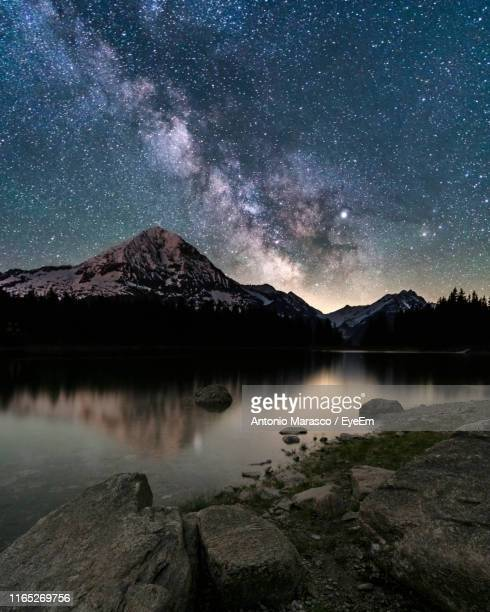 scenic view of lake by mountains against sky at night - swiss alps stock pictures, royalty-free photos & images