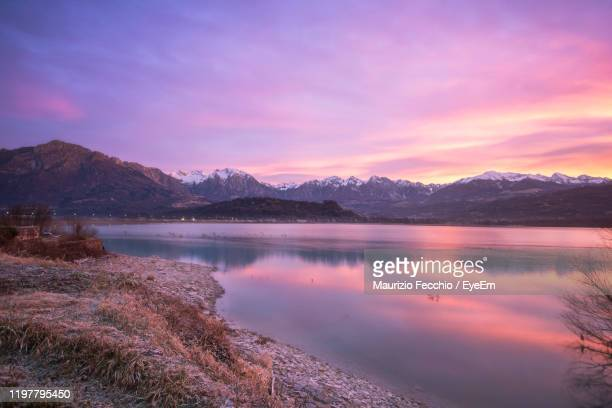 scenic view of lake by mountains against sky during sunset - maurizio fecchio foto e immagini stock