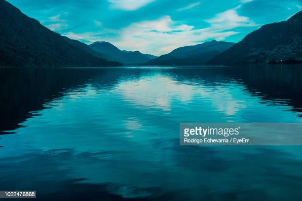 scenic view of lake by mountains against sky - petrohue river stock photos and pictures
