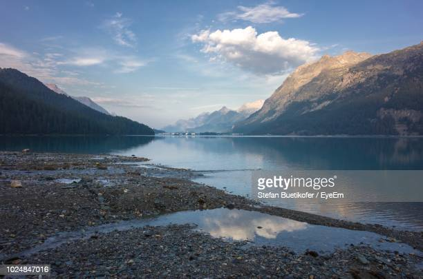 scenic view of lake by mountains against sky - seeufer stock-fotos und bilder