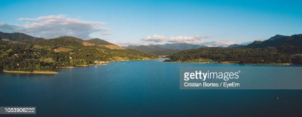 scenic view of lake by mountains against sky - bortes foto e immagini stock