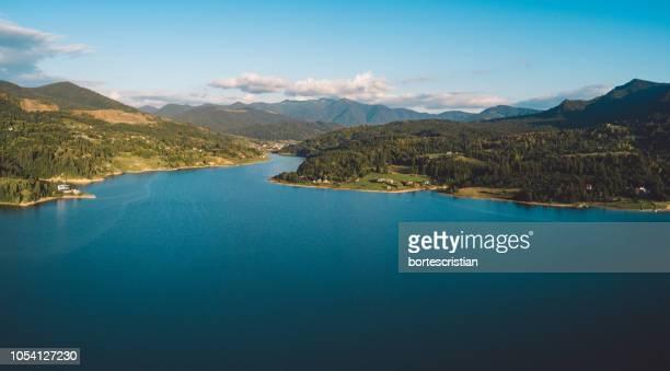 scenic view of lake by mountains against sky - bortes fotografías e imágenes de stock