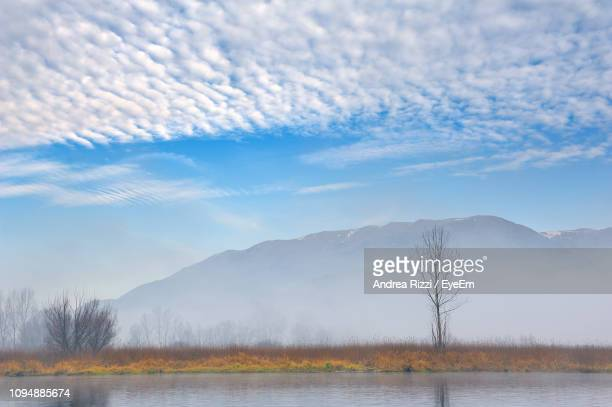 scenic view of lake by mountains against sky - andrea rizzi fotografías e imágenes de stock