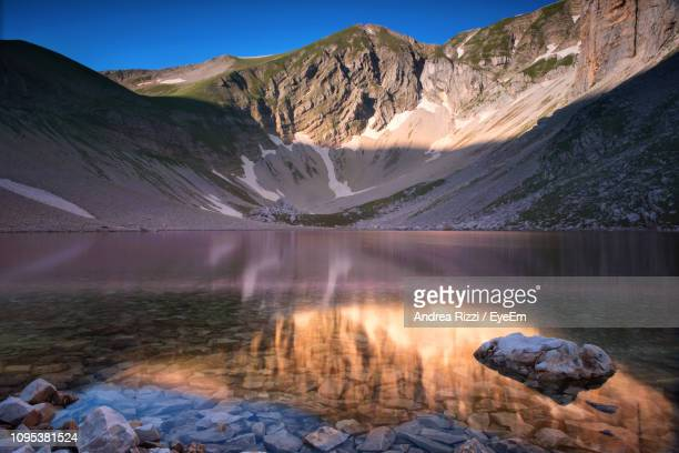 scenic view of lake by mountains against sky - andrea rizzi stockfoto's en -beelden