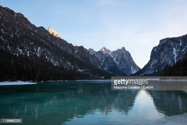 scenic view of lake by mountains against sky - massimo cavallari stock pictures, royalty-free photos & images