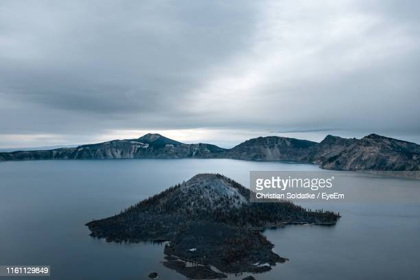 scenic view of lake by mountains against sky - christian soldatke stock pictures, royalty-free photos & images