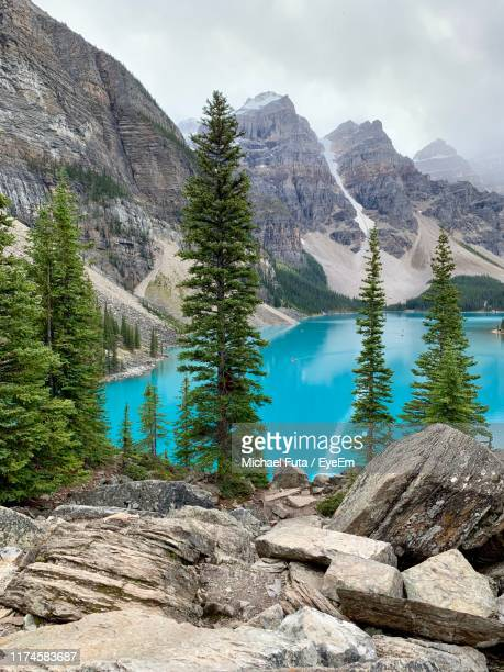 scenic view of lake by mountains against sky - futa stock photos and pictures