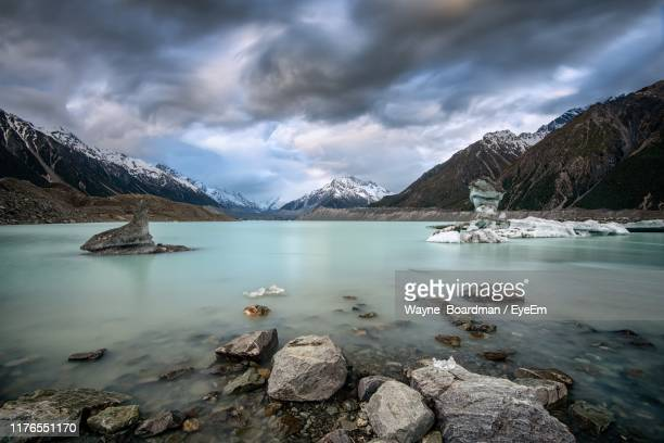scenic view of lake by mountains against sky - wellington new zealand stock pictures, royalty-free photos & images