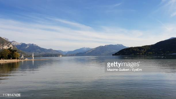 scenic view of lake by mountains against sky - annecy photos et images de collection