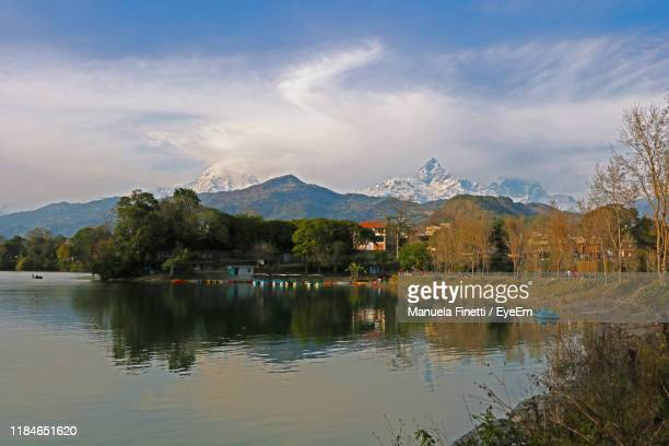 scenic view of lake by mountains against sky - pokhara stock pictures, royalty-free photos & images