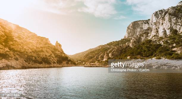 scenic view of lake by mountains against sky - calanques stock pictures, royalty-free photos & images