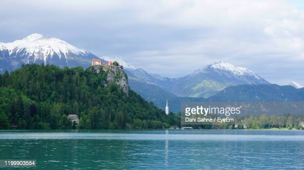 scenic view of lake by mountains against sky - sahne ストックフォトと画像