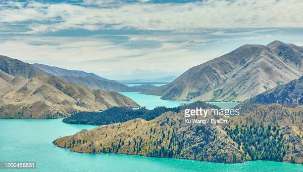 scenic view of lake by mountains against sky - wang he stock pictures, royalty-free photos & images