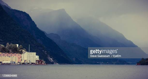 scenic view of lake by mountains against sky - steve guessoum stockfoto's en -beelden