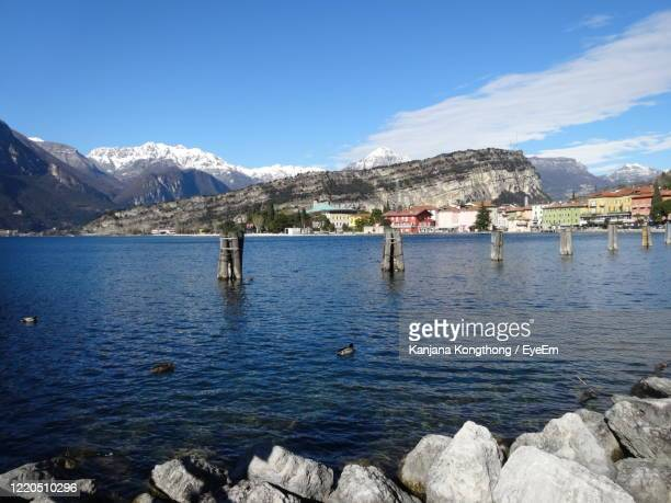 scenic view of lake by mountains against sky - kanjana kongthong ストックフォトと画像