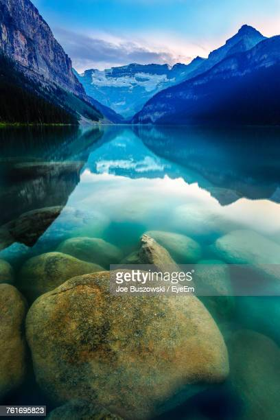 scenic view of lake by mountains against sky - lake louise lake stock photos and pictures